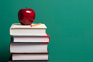 Image of books piled up with an apple on top