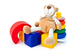 Image of a teddy bear sitting on top of some toy blocks
